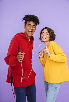 Веселая многонациональная подростковая пара, стоящая вместе изолированно, слушает музыку в наушниках и держит мобильный телефон