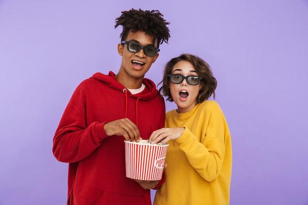 Веселая многонациональная подростковая пара стоит вместе изолированно, смотрит фильм и ест попкорн