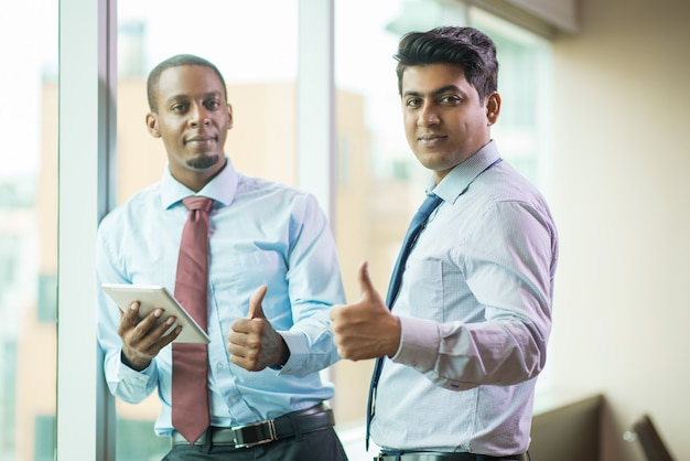 Cheerful multi-ethnic business executives showing thumbs-up