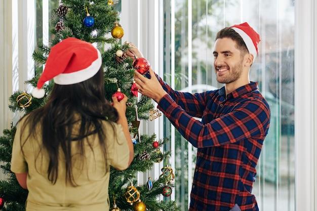 Веселые многонациональные деловые люди украшают елку в офисе красочными безделушками