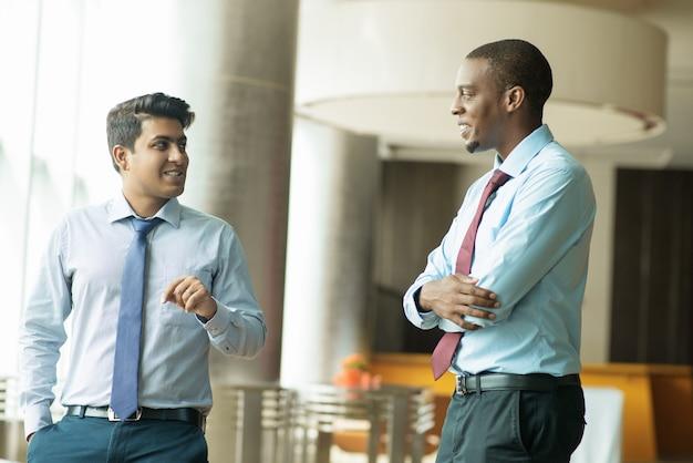 Cheerful multi-ethnic coworkers talking during short break