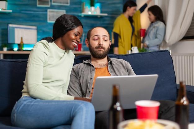 쾌활한 다민족 친구들이 소파에 앉아 놀고 있는 노트북에서 재미있는 비디오를 보고 있습니다. 배경에서 맥주를 마시는 두 여성은 엔터테인먼트 파티에서 함께 시간을 보낸다.
