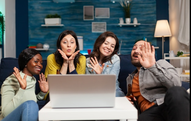 Cheerful multi ethnic friends waving at camera during online internet video call conference while having fun. group of multiracial people spending time together sitting on couch