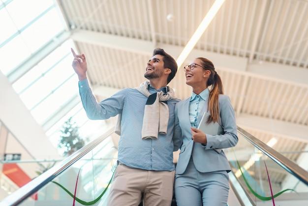 Жизнерадостные пары многокультурного одели элегантное положение на эскалаторе и смотреть вверх.