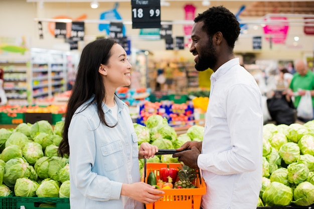 Cheerful multiethnic couple in grocery store
