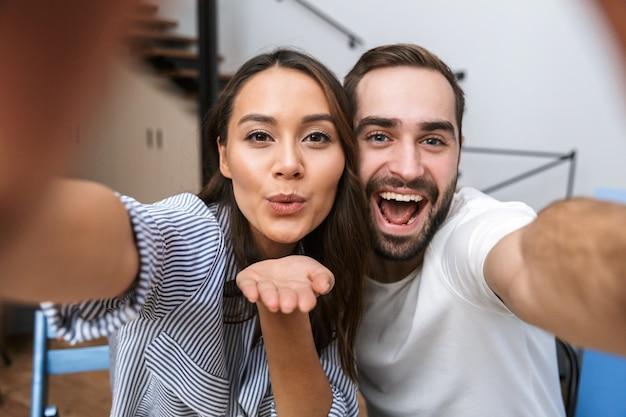 Веселая многонациональная пара делает селфи, сидя на кухне