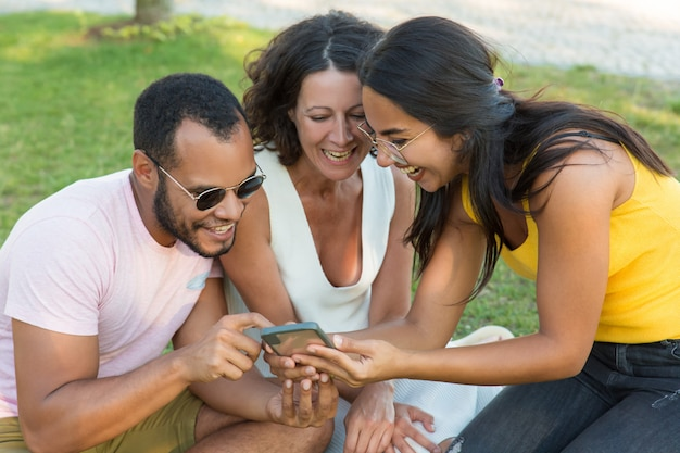 Cheerful multiethnic friends using smartphone