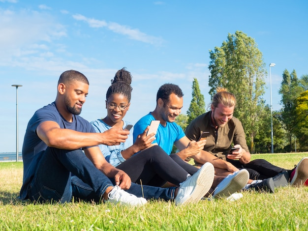 Cheerful multiethnic friends using smartphones in park