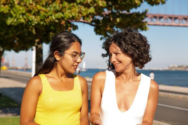 Cheerful multiethnic women walking at riverside