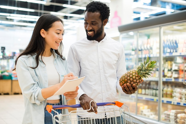 Cheerful multiracial couple buying goods in supermarket