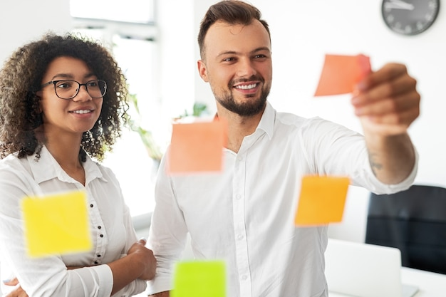 Cheerful multiracial man and woman smiling and checking sticky notes on glass wall during meeting in modern workplace