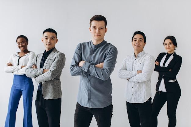 Веселые многорасовые профессиональные деловые люди смеются вместе, стоя в ряду возле стены, счастливые разнообразные молодые сотрудники, группа студентов, корпоративная команда сотрудников, с удовольствием, концепция человеческих ресурсов