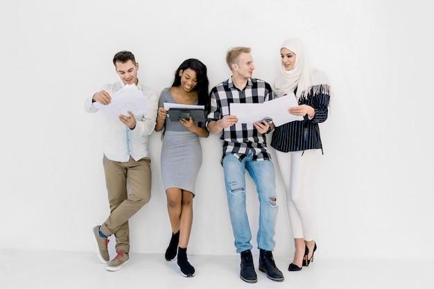 쾌활한 다민족 전문 비즈니스 사람이나 학생들이 웃고 함께 흰 벽 배경에 서 이야기