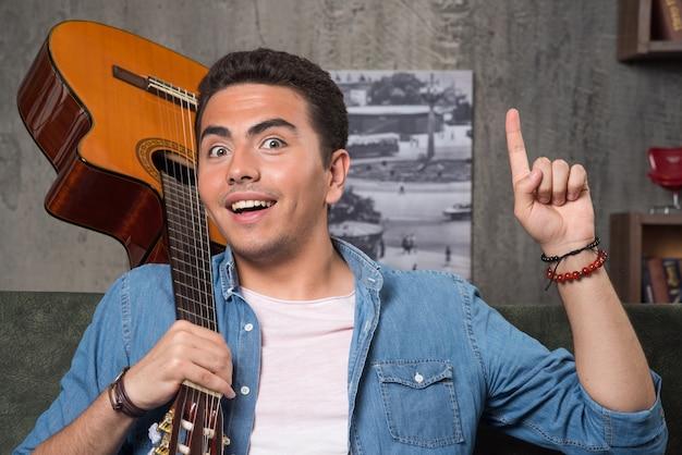 Musicista allegro che tiene una bella chitarra e che si siede sul divano. foto di alta qualità