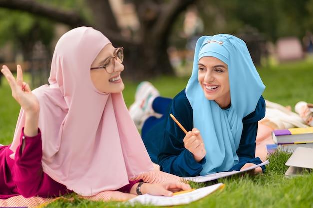 陽気なイスラム教徒の学生。草の上に横たわって一緒に勉強しながら素晴らしい気分の陽気なイスラム教徒の学生