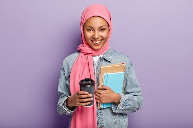 Cheerful muslim woman in pink hijab, denim coat, carries pocketbook