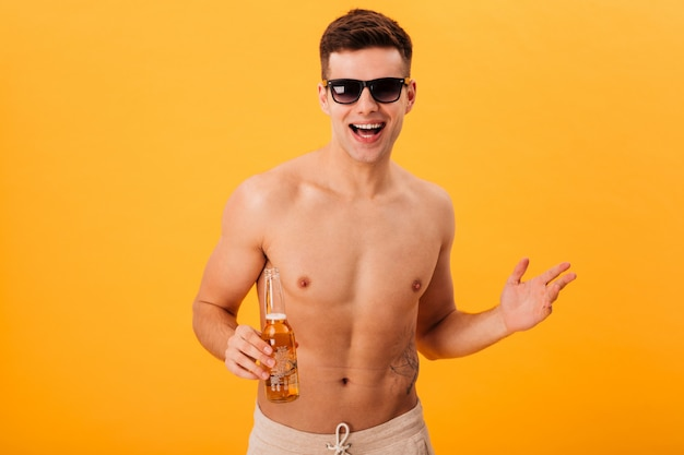 Cheerful naked man in shorts and sunglasses holding bottle of beer