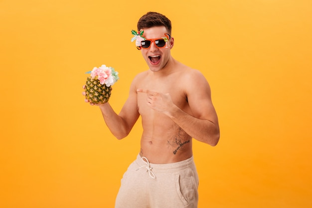 Cheerful naked man in shorts and unusual sunglasses holding cocktail while pointing on it and looking at th camera over yellow