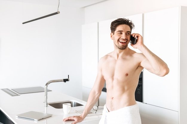 Cheerful naked man standing indoors at kitchen