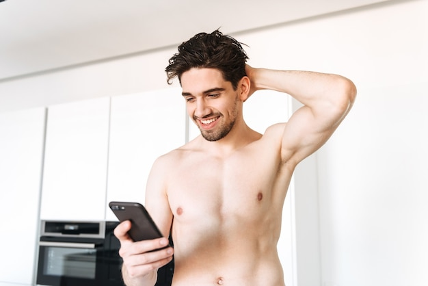 Cheerful naked man using mobile phone.