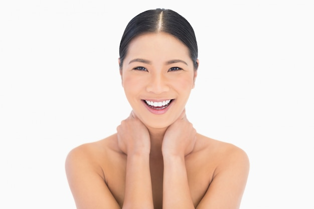 Cheerful natural model posing touching her neck