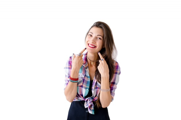 Cheerful natural woman pointing with fingers on cheeks