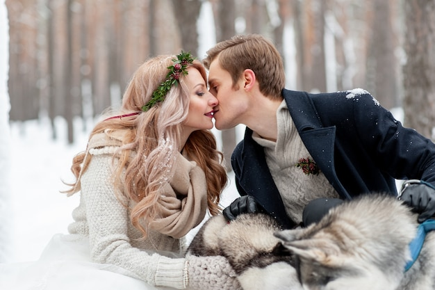 Cheerful newlyweds are kissing on background of husky. winter wedding. copy space