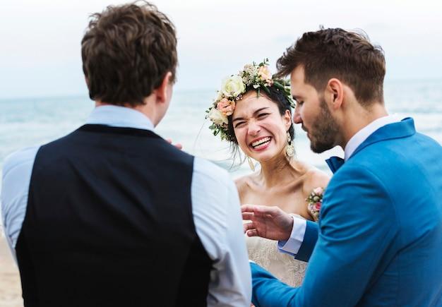 Cheerful newlyweds at beach wedding ceremnoy