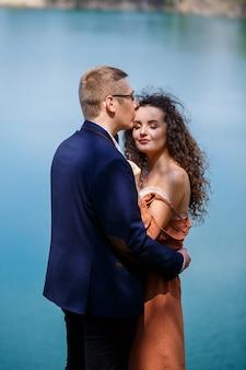 陽気な新婚夫婦は、湖と緑の牧草地を背景に、手をつないで笑いに行きます。陽気な新郎と巻き毛の美しい花嫁が牧草地を歩く