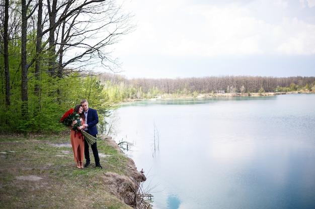 Cheerful newlyweds go holding hands and laughing, against the background of a lake and a green meadow. cheerful groom and beautiful bride with curly hair walk in the meadow