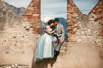 Cheerful newlyweds pose on the ruins of old fortress in the sunny day