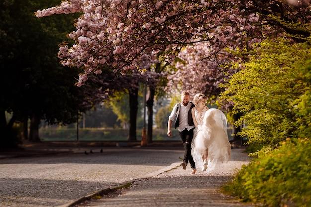 陽気な新婚夫婦が街を駆け巡り、花の咲く木々に囲まれて幸せ。新婚夫婦は、美しい街で時間を過ごす楽しみを持っています。春の結婚式。感情的なカップル。セレクティブフォーカス
