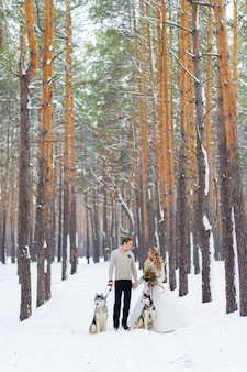 Cheerful newlyweds walks on the trail in the snowy forest with two siberian dogs.