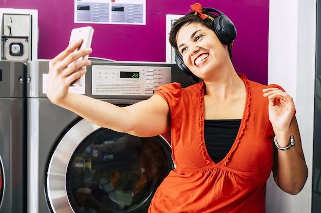 Веселая милая красивая молодая дама с черными волосами слушает музыку в наушниках, принимая селфи с телефоном.