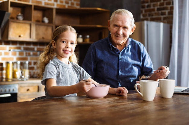 Cheerful nice little girl eating cereal while enjoying her breakfast with grandfather
