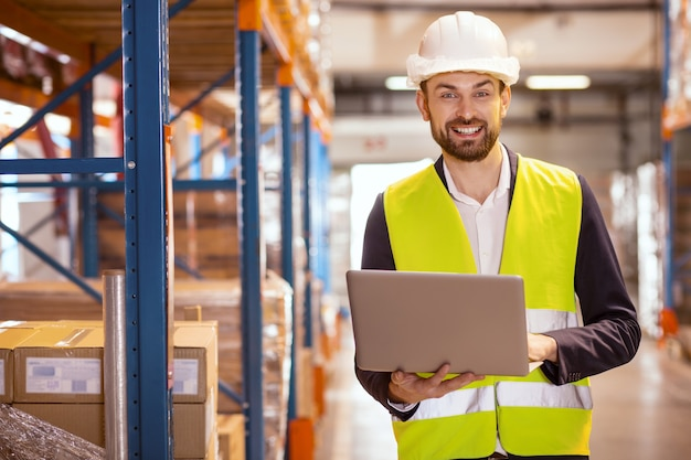 Cheerful nice man smiling while dealing with logistics system in the storehouse
