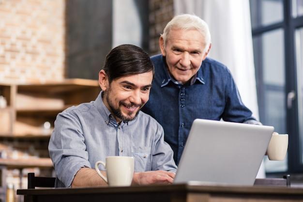 Веселый приятный человек с помощью ноутбука со своим отцом, отдыхая вместе дома