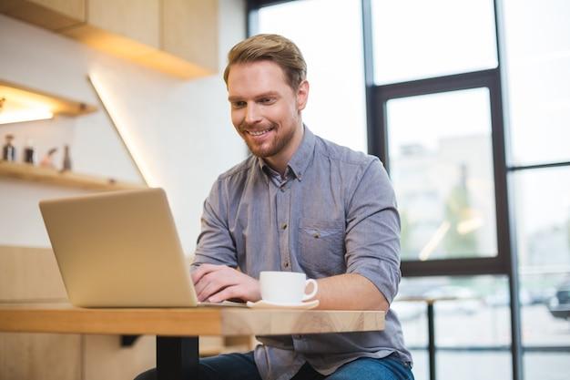 テーブルに座って、フリーランスでありながらラップトップで作業している陽気な素敵な前向きな喜びの男
