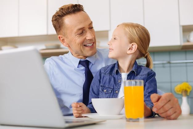 Веселый приятный позитивный мужчина сидит перед ноутбуком и смотрит на своего ребенка, заботясь о ней