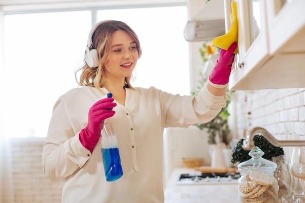 Веселая милая женщина, держащая моющее средство для стекла, убирая свою кухню
