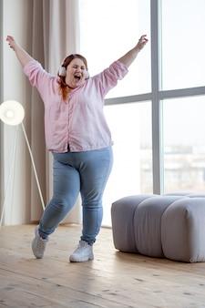 Веселая милая женщина показывает свои положительные эмоции во время танца под музыку