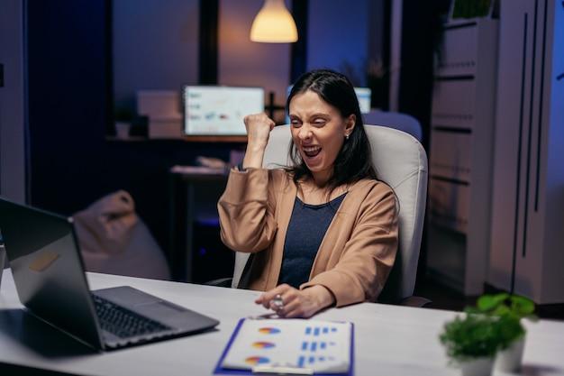 쾌활한 기업가, 초과 근무하는 랩톱에서 멋진 온라인 뉴스를 읽고 황홀함을 느낍니다. 성공적인 프로젝트 때문에 사무실에서 늦은 밤 근무하는 흥분된 여성.