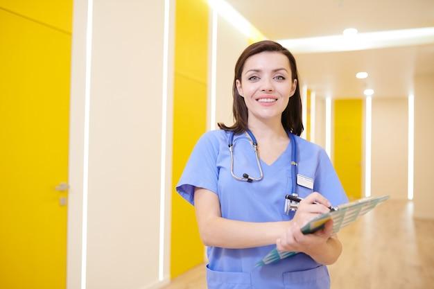 クリニックで陽気な看護師ポーズ