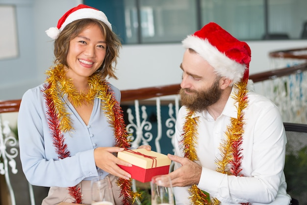 Cheerful office assistant in santa hat giving christmas gift