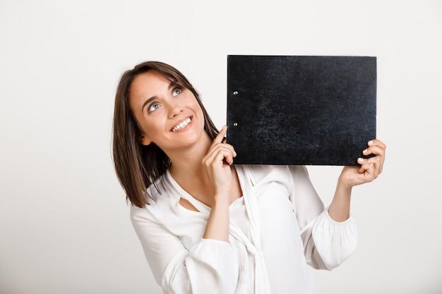 Signora allegra dell'ufficio che mostra insegna sulla lavagna per appunti nera