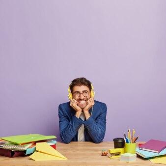 Веселый офисный работник слушает музыку на рабочем месте через стереонаушники, одетый официально
