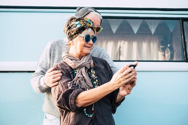 Веселая старая кавказская взрослая пара использует технологический смартфон в интернете, чтобы сделать селфи для аккаунтов в социальных сетях, веселые люди со старым винтажным синим фургоном для путешествий