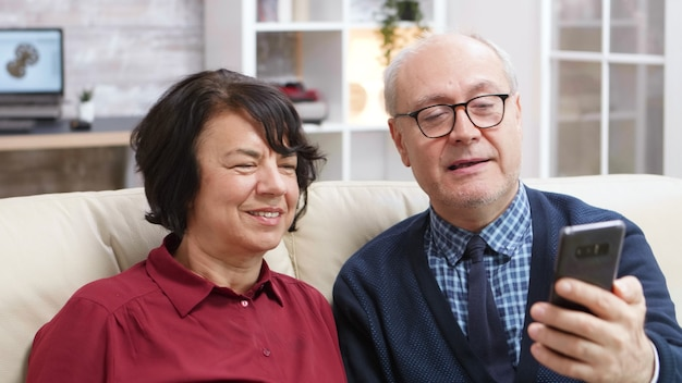 Cheerful old couple sitting on sofa taking a selfie in living room.