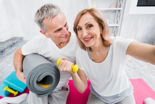 Cheerful old couple taking self portrait holding yoga mat and dumbbells in hand
