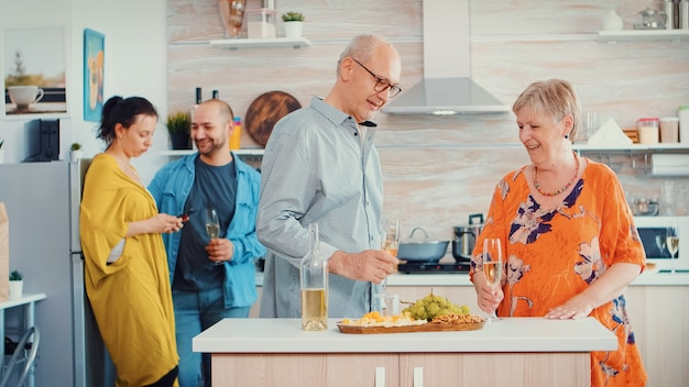 Cheerful old elderly adult family hugging laughing dancing drinking a glass of white wine in front young couple. in the kitchen. grandma and grandpa embracing smiling and daughter taking a photo